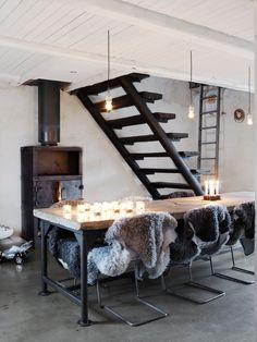 Matbordet har de själva gjutit av material från skroten. Den patinerade 30-talskaminen från Nacka byggnadsvård värmer hela huset vintertid. Trappan leder till kombinerat vardagsrum och kontor på övervåningen.