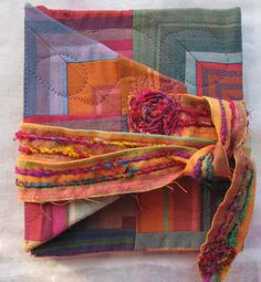 This journal cover was created from some old quilt blocks that were made from a stash of Kaffe Fassett fabric.  The tie is a strip from that same fabric with silk sari yarn sewn on for texture.