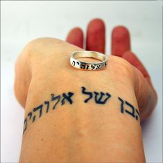 """A ring hand stamped in Hebrew with the text, """"child of God"""". The story behind this ring is best told on Lisa's blog. It is a story of depression. It is a story of strength. Lisa says: This ring is a reminder of who I belong to. That my creator loves me. Even when I cannot love myself. You can read the whole story here: http://blog.studiojewel.com/2011/04/depression-hebrew-and-a-new-ring/ Product Details - sterling silver - 4mm wide / 1.5mm thick Each piece is handcrafted in our Grand Haven…"""