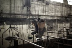 Boots hang in a changing room in the partially abandoned and closed Santiago mine, as a result of the coal crisis, near Mieres, Oviedo, Spain, Monday, June 18, 2012. Spanish coal mining unions are waging a general strike as 8,000 mineworkers at over 40 coal mines in northern Spain continue their protests against government action to cut coal subsidies. EMILIO MORENATTI - AP