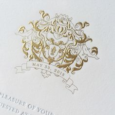 We're making a slight departure from our regular #MonogramMonday posts with this gorgeous gold engraved family crest! We love the way it elegantly displays the wedding date atop the invitation! | Bell'INVITO Stationers