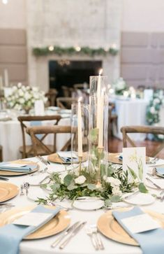elegant simplicity in this reception centerpiece of eucalyptus and olive leaf greenery nestled within a trio of brass candlesticks with ivory taper candles and a custom watercolor table number. Round Table Centerpieces, Greenery Centerpiece, Wedding Table Centerpieces, Wedding Table Settings, Wedding Decorations, Round Table Settings, Candlestick Centerpiece, Wedding Ideas, Centerpiece Ideas