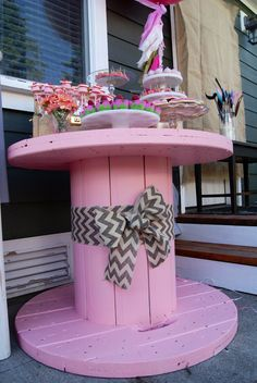 Giant pink spool as a dessert table for a party. Could repaint for everyday use.