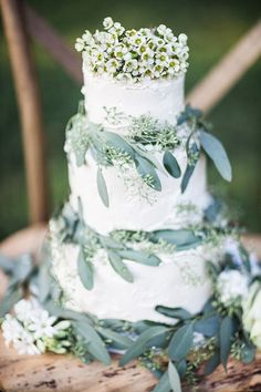 Chapel Hill bake shop Sugarland created this beautifully simple spring wedding cake, elegantly wreathed with seeded eucalyptus and topped with a cluster of tiny blooms. | Photo by Sara Logan Photography