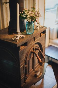 A vintage heating stove in a Bluebird school bus with a blue vase of wildflowers on top.