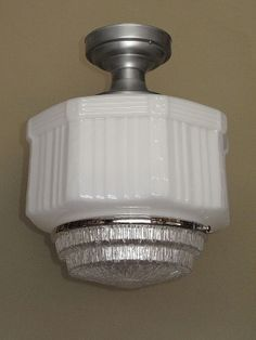 Large size 1920s vintage school house or department store electric ceiling fixture with neo-classical design elements. Milk Glass body has banding along its top edge with rosettes at each top corner. Under the rosettes a floral ribbon separates each panel of vertical ribs. Shown on a brushed metal ceiling fitter  http://www.vintagelights.com/product/1/large-vintage-schoolhouse-style-electric-ceiling-fixture.html
