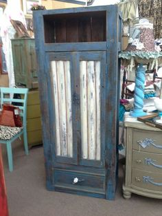 "$149 - This is a primitive 2 door cabinet with shelves inside and a single drawer in the base. One open shelf in the top section gives additional display area. Painted blue and distressed with the doors an accenting cream color. The cabinet measures 28"" by 16"" by 68"". It can be seen in Booth D8 at Main Street Antique Mall, 7260 E Main St ( E of Power), Mesa, AZ 85207 - 480-924-1122 -Open 7 days a week 10a.m. to 5:30p.m. - Cash, Charge or 30 day layaway also available."