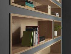 perlgraue Regale mit Nischen aus Holz voller Bücher und eine Vase