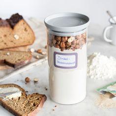 Du backst dein Brot nicht selbst? Solltest du aber! Einfach Brotbackmischung mit Hefe, Wasser und Honig mischen und als Dinkel-Haselnussbrot genießen.