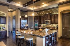 Transitional elements with accents of warm gold and olive tones. Rich java cabinets and granite anchoring the home creating a great place for entertaining.   Ashton Woods