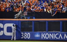 Kansas City Royals center fielder Lorenzo Cain stood at the outfield wall as fans stretched to catch a first inning solo home run ball hit by New York Mets right fielder Curtis Granderson during game five of the World Series on Sunday, November 1, 2015 at Citi Field in New York.