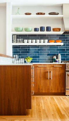 The residents have a particularly strong sense of color and love to cook with their son, so no-fuss finishes likes these blue tiles from Heath Ceramics were an ideal choice. The tiles combine with colorful tableware and custom walnut cabinetry to make a vibrant inteiror.