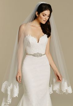 Ivory net trumpet bridal gown, Alencon lace bodice with deep sweetheart neckline, satin ribbon belt with beaded applique at natural waist, hem lace detail with a scalloped tiered cathedral train. Shown with matching veil: V601