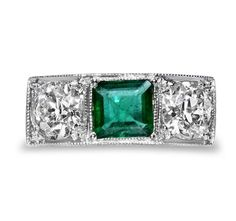 A handmade three stone Art Deco emerald and diamond ring. The brightly coloured emerald is contrasted with two large old European cut diamonds, bead set in a geometric platinum setting. Platinum being the prominent metal of the 1920/30s, has been exquisitely engraved with a geometric pattern.