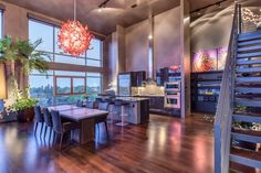 A modern kitchen with sleek eat-up bar opens up to a dining area and living area.