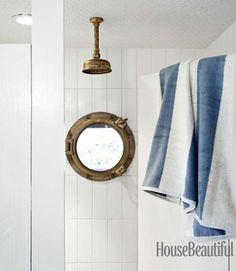 beach house shower with brass porthole window and waterworks rainfall shower head | Erin Martin Design