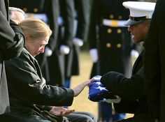 Kelly Hugo, left, recieves a flag that covered her son's casket during a burial service for Marine Cpl. Sean A. Osterman at Arlington Cemetery on Jan. 4, in Arlington, Va. Osterman, 21-years-old, from Princeton, Minn., was wounded on Dec. 14 in Afghanistan and died two days later in Landstuhl Medical Center at Ramstein Air Force Base in Germany, according to reports.