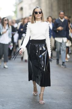 Olivia's skirt and sweater combo may seem demure, but with a patent finish on her skirt and lace-up detaili...