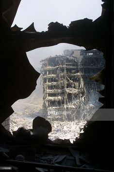 The wreckage of the World Trade Center is visible through the broken window of an apartment building near the wreckage September 13, 2001 in New York City, two days after two airplanes slammed into the twin towers September 11, 2001 in an alleged terrorist attack.