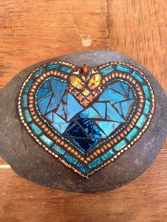 This mosaic rock incorporates a beautiful vintage jewel piece which is highlighted by the stunning blue mirror glass center. This one -of -a -kind rock measures and is grouted. Mosaic Stones, Mosaic Rocks, Mosaic Art, Mosaic Glass, Glass Center, Mosaic Ideas, Blue Mirrors, Garden Stones, Stained Glass Art