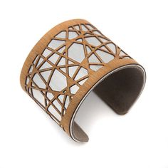 Laser cut cuff bracelet in cherry wood. I laser cut a pattern of geometric abstract lines into real wood and layered it over a brushed aluminum metal