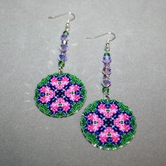 Silver earrings with a pansy and bleeding heart mandala sacred geometry charm titled Love Struck. <br /> <br />These lightweight, dainty silver earrings begin with a dangle of green Czech glass beads and lavender crystals that accentuate the colors in the mandala charm that has scalloped edges that catch the light. The mandala charm is 1 – ¼ inch in%...