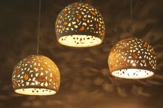 A cluster of  ceramic pendant lights with warm yellow and orange colored porcelain. Hanging light.