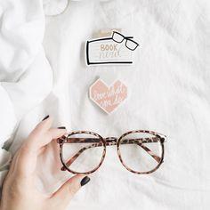 Foto clean com fundo branco: dois marcadores magnéticos de livro e óculos de grau.