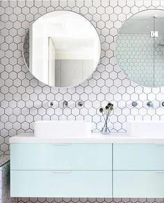 Lichte Scandinavische badkamer met hexagonale tegelmuur, lichtblauw badkamermeubel en ronde spiegels. Perfect plaatje!