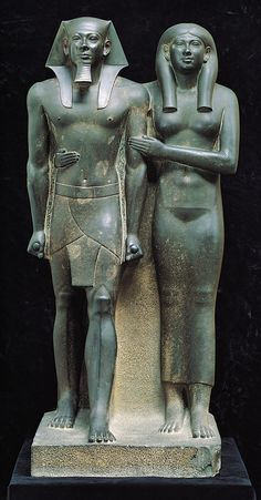 "One of the most well recognized Ancient Egyptian statues Menkaure and his Queen, Dynasty IV, ca. 2490–2472 BC. Graywacke, approx. 4' 6 1/2"" high. Currently located at the Museum of Fine Arts, Boston.  Menkaure is portrayed in the familiar Egyptian pose standing as if at attention with his left leg extended forward, his arms held stiff at his sides, and his fists clenched holding some unidentified cylindrical objects. His stance appears assertive, indicative of his power.  The statue is a…"