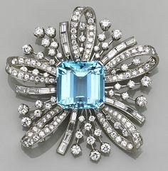 An aquamarine, diamond and platinum spray brooch, circa 1950  centering a square-cut aquamarine within a ribbon-like spray of round brilliant and baguette-cut diamonds; aquamarine weighing an estimated: 19.50 carats; estimated total diamond weight: 8.20 carats...