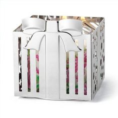 Create a perfect Yuletide display to enhance your festive fragrances with our Holiday gift box shaped candle holder. The charming silvertone ribbon bow with nickel plating beautifully reflect light for a merry atmosphere.