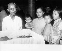 Vietnamese Farmers Victims Of Viet Cong Midnight Raids - Nguyen Van Buong (shown in casket) was a 38-year-old rice farmer and the father of three children. His wife and aged father are shown standing around his casket in their thatched-roof, dirt-floored, one room home.