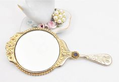 Lions Gold Tone Hand Mirror, Ornate Frame and Handle, Lions Club International Measures 4 3/4 long and 2 1/4 wide mirror. A lovely little mirror, with a small Lions International logo on the handle. Ornate gold tone metal scrolling with hearts on the handle and flowers at the top of the frame. This small hand held mirror, is a nice Lions collectible. I have other collectibles from this club as well, listed in the shop. The mirror has little wear and silvering, a couple of small d...