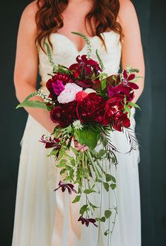 A cascading red bouquet comprised of garden roses, anemones, and clematis   created by Statice Couture   via brides.com