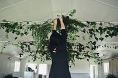 vine and greens hanging from 2 long horizontal beams in venue