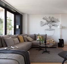 Mirroring the palette of the kitchen shelving, a large graphite frame lines the windows in the living room, which is furnished with a sectional by Casadesus, two Nelson coffee tables by Vitra, and a rug by Materia shop. The hanging artwork is a steel sculpture by Frank Plant.