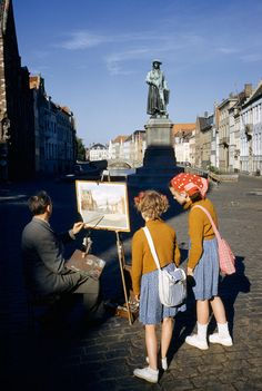 Girls watch artist painting picture of statue of Flemish artist in Bruges, Belgium, May 1955. Photograph by Luis Marden, National Geographic