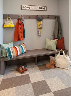 Gray mudroom features gray walls with white moldings lined with a long wood bench under a row of hooks alongside a multi-colored tiled floor.