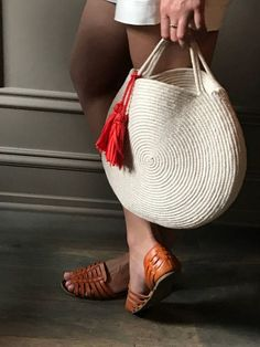 Round purse made out of natural cotton rope, in a winter white to highlight your wardrobe. This bag is durable and roomy enough to fit all your necessities - measures about 12 inches across and 2 inches deep, with about 3 inch handles. The bag in the first photo is the one I carried with