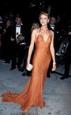 Oscars 2000 - Charlize Theron set the red carpet ablaze in a plunging tangerine bias-cut chiffon gown designed by Vera Wang.  This was another most memorable Oscar look.  , She also wore a pair of Fred Leighton diamond clips and diamond bracelet.