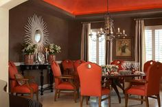 Dark chocolate walls create a sophisticated backdrop to this dramatic dining room. A bold orange ceiling is reflected in the upholstered chairs that surround the traditional dining table. An elegant chandelier brings a touch of Old World glamour to the space.