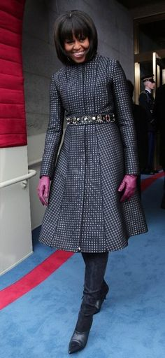 Michelle Obama wore a navy Thom Browne coat and dress, which the White House said was developed based on the style of a man's silk tie. The boots were by designer Reed Krakoff.