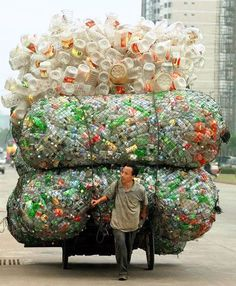 A Chinese man transports plastic bottles and containers for recycling in Haikou, the capital of China's southern Hainan province. Plastic Pollution, Bizarre, Wise Owl, People Of The World, Go Green, Green Girl, Plastic Bottles, Water Bottles, Empty Bottles