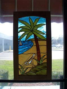 Stained glass window depicting a scene of a beach chair and palm tree. Custom made for a kitchen cabinet. Created by Designer Art Glass Daytona Beach Fl. 407 328 8683