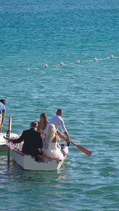 La sposa raggiunge la spiaggia a bordo di una barca, lo sposo attende assieme agli invitati il suo arrivo. Hotel Gabbiano Azzurro - Golfo Aranci