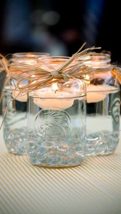 Easy fall decorations: mason jars with floating candles (any color works), and raffia tied around the rim of the jar
