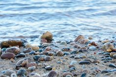 A calm day along the shore of Lake Superior with a variety of colorful rocks in the foreground.