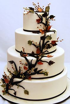 Brides.com: Fall Wedding Cakes. This wedding cake is decorated with brown satin ribbon wrapped around the base of each tier and cascading leaves and berries fashioned from gumpaste.  Cake design by Pink Cake Box