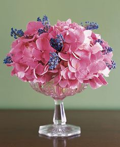 Hydrangeas & Grape Hyacinths  Pink hydrangeas and grape hyacinths clustered in a crystal compote make for a supremely simple arrangement. A hidden grid of floral or transparent tape across the top of the bowl supports the cloud of blooms